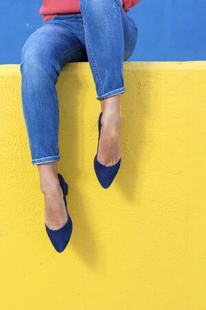 Closeup view of woman heels. Woman in jeans sitting on a yellow wall outdoors.