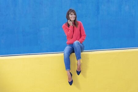 Woman in jeans sitting on a yellow wall while looking away