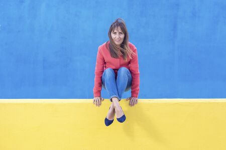 Woman in jeans sitting on a yellow wall while looking camera