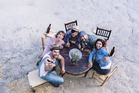 Aerial view of a group of friends sitting around a table holding beers