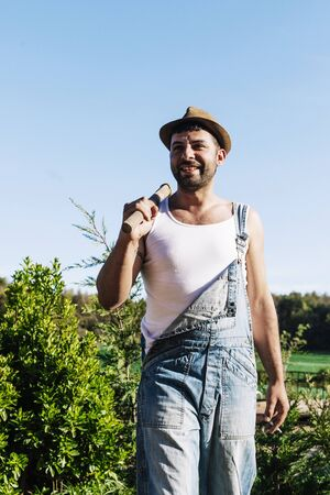 Smiling young farmer man standing in the garden while looking away Stock Photo