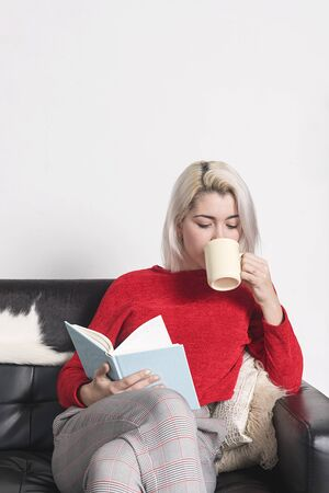 Caucasian woman sitting on sofa drinking coffee and reading book Banco de Imagens