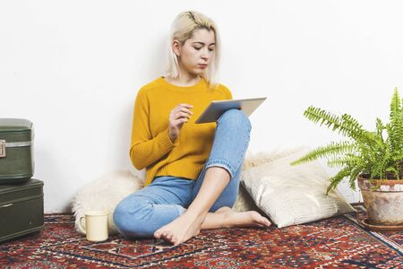 Portrait of blonde woman sitting on the floor of living room using digital tablet