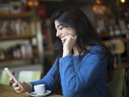 Young woman talking through video-chat in her smartphone while sitting in cafe Banco de Imagens
