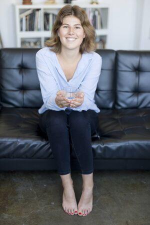 Chica bebiendo agua sentada en un sofá en casa y mirando a cámara.