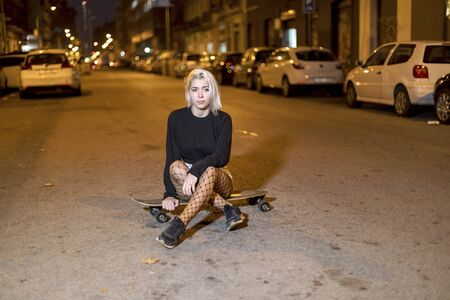 Young woman in shorts on a long board while looking camera at night in the city 版權商用圖片 - 131761227