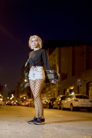Young pretty woman looking camera in shorts while standing on the street holding a skateboard at night in the city