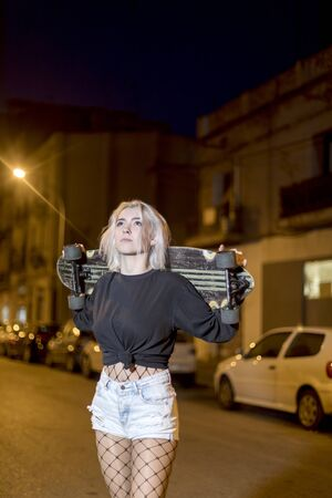 Young pretty woman looking camera in shorts while standing on the street holding a skateboard at night in the city 版權商用圖片 - 131761534