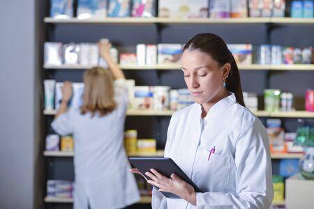 Jonge apotheker die naast medicijnplanken staat en tablet vasthoudt Stockfoto