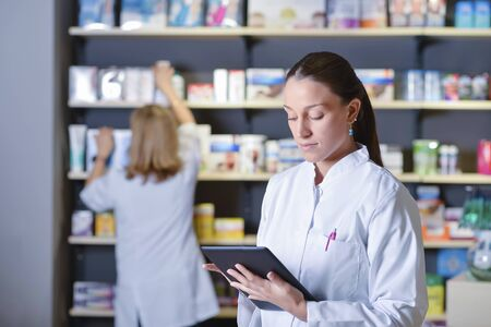 Joven farmacéutico de pie junto a los estantes de la medicina, sosteniendo la tableta Foto de archivo
