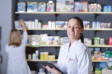 Joven farmacéutico de pie junto a los estantes de la medicina, sosteniendo la tableta