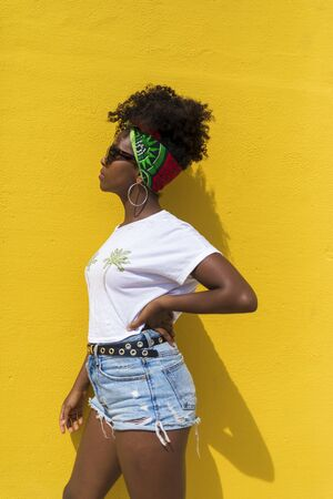 Side view of an afro woman with sunglasses and headscarf leaning on yellow wall while looking aside