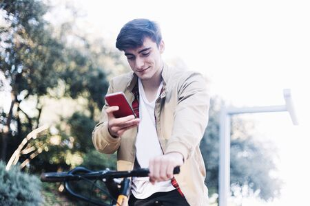 Young guy on a bicycle looking at mobile phone.