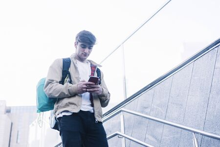Young man walking down stairs with backpack while using mobile outdoors