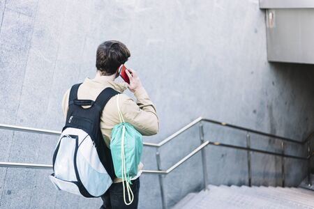 Young man walking down stairs with backpack while using mobile outdoors Imagens
