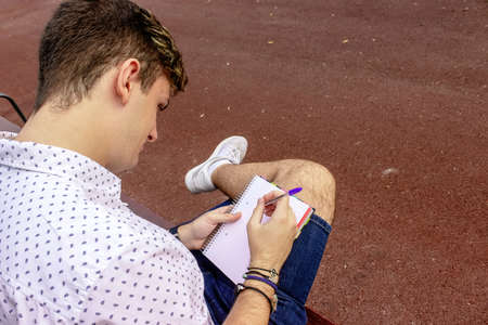 Teenager male sitting on a bench while writing on a notebook