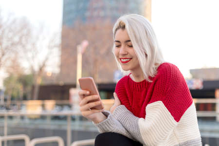 Close up portrait of beautiful young girl using cellphone outdoors in the city 免版税图像