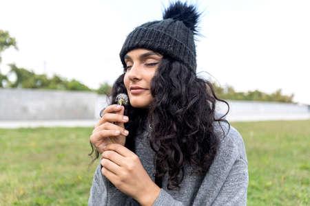 Beautiful brunette smelling a dandelion ( dark hair woman )