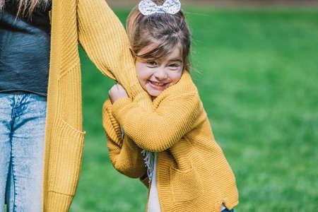 Pretty smiling little child girl standing in park outdoors. 免版税图像