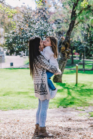 Little cute child baby girl kiss on cheek and hug, embrace with happy pretty woman in green park. 免版税图像