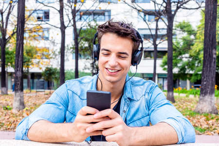 Young smiling man looking at smartphone with headphone on his head 免版税图像