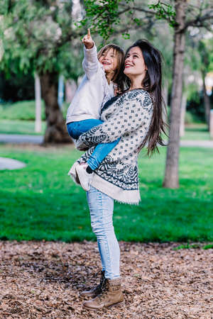 Mother holding her daughter and playing around park on beautiful morning.