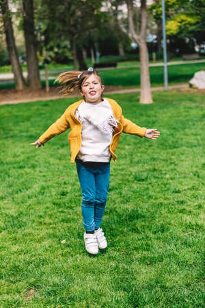 Pretty little girl jumping over the rope in the park on sunny day