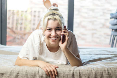 Close-up portrait of a nice sweet winsome attractive charming cute lovely adorable stunning cheerful blond lady lying on bed taking b y phone