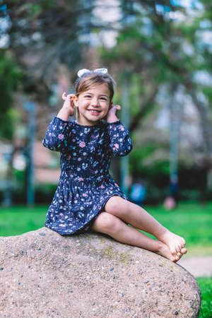 Pretty smiling little child girl sitting in park outdoors.