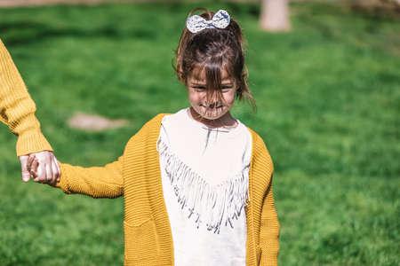 Sad girl is standing on green park holding mom hands 免版税图像