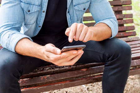 Attractive young man sitting on a bench outside using his cell phone wearing a hat and a purple shirt and jeans. 免版税图像