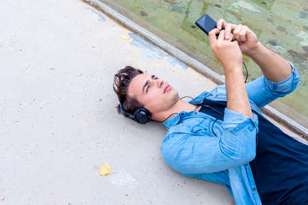 Young guy listening music by smartphone lying down with camera on outdoors ground, Happy life, Lifestyle