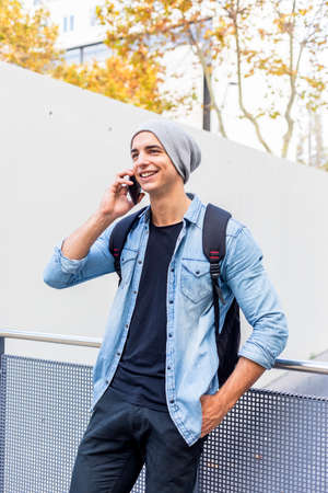 Urban stylish man standing by the wall using cellphone