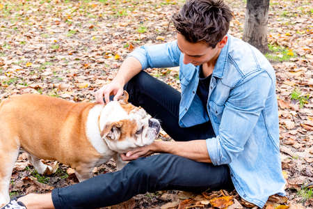Young guy sitting on park ground with his dog