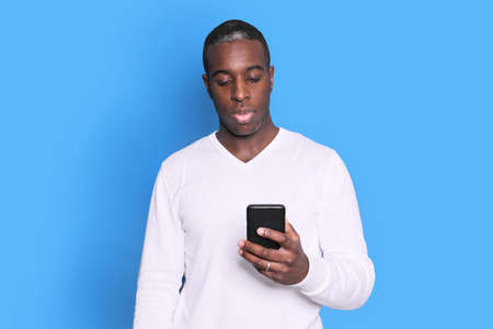 Cheerful African American man in white sweater using smartphone application. 免版税图像