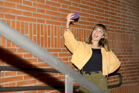 Beautiful young stylish woman walking in the night city streets using smartphone.