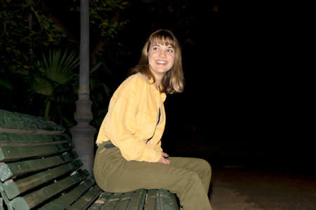 Young beautiful woman sitting in a bench in a public city park at night while looking to camera 免版税图像