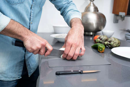 Cropped view of male cutting vegetables on chopping board in kitchen