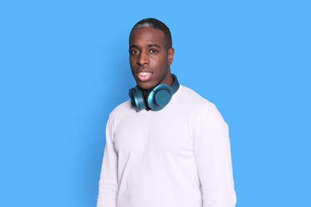 A Handsome dark skinned man with headphones around his neck while looking away against blue background