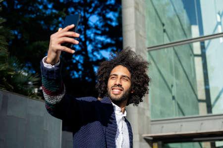 Portrait of smiling afro man taking selfie outside in city