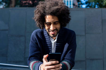 Portrait of handsome afro man using his mobile in the street. 免版税图像