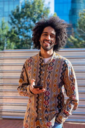 Young afro man using his smartphone with smile while standing outdoors in sunny day