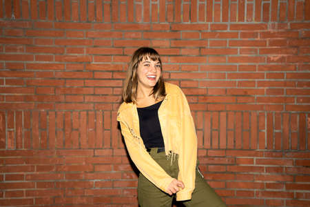 Beautiful young woman stands near an old brick wall in the city at night
