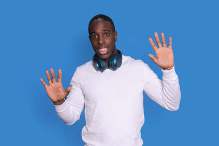 Perplexed black man guy in white street wear sweater posing isolated on blue background, rising hands up, showing palms