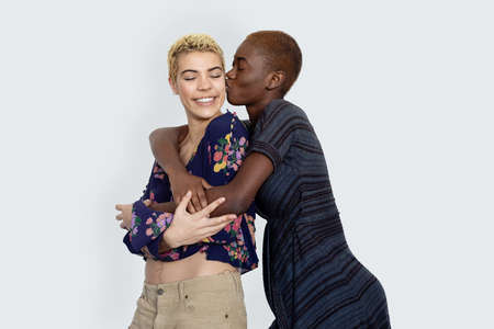 Photo of joyful ladies kissing and embracing togetherness, being of different of races, dressed in casual clothes.