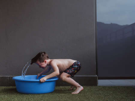 children in swimsuits and wet playing with water on a terrace