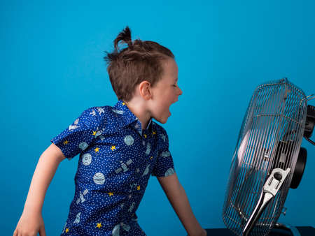 child cooling off in front of a fan and blue background screaming and singing