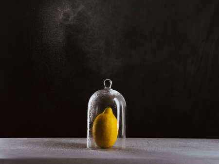 glass dome that keeps a lemon. drops of water come out of a spray