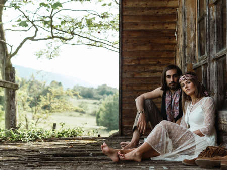 HETEROSEXUAL COUPLE WOODSTOCK HIPPIE, ADMIRED SITTING ON THE PORCH OF THEIR HOME. WOODEN CABIN IN THE FOREST Imagens