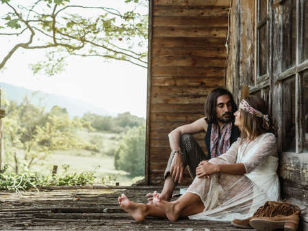 HETEROSEXUAL COUPLE WOODSTOCK HIPPIE, ADMIRED SITTING ON THE PORCH OF THEIR HOME. WOODEN CABIN IN THE FOREST